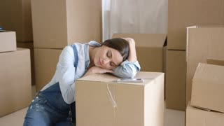 Young woman taking a nap on a brown carton as she relaxes for a break while packing and moving her home