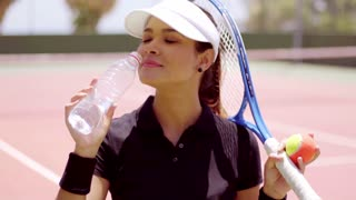 Young woman tennis player taking a break to drink a bottle of fresh water at the side of the court to quench her thirst
