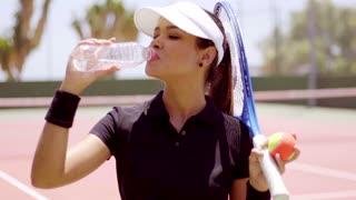 Young woman tennis player taking a break