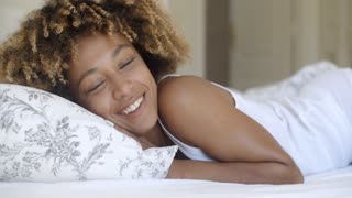 Young Woman Waking Up From Sleep And Smiling