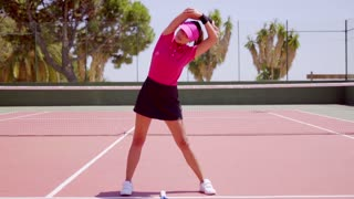Young woman warming up before a game of tennis standing on an outdoor court doing stretching exercises with raised arms