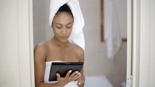 Young Woman Wearing Bath Towel Using Tablet Computer