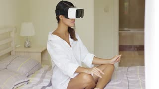 Young woman wearing virtual reality glasses gesturing with her hands as she interacts with her simulated environment while relaxing on her bed