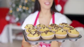 Young woman with a tray of freshly baked Christmas cupcakes decorated with chocolate in a close up view of the cookies