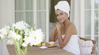 Young woman wrapped in fresh white towels sitting having breakfast on her patio and smiling at the camera