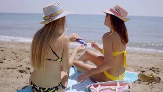 Young women applying sunscreen