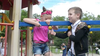 A boy talking with girl playing together on the playground in the park