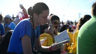A girl reads a book in the crowd
