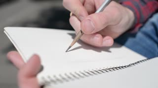 A man draws a pencil sketch in a notebook - close-up detail