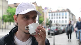 A man drinks coffee on a Milan street
