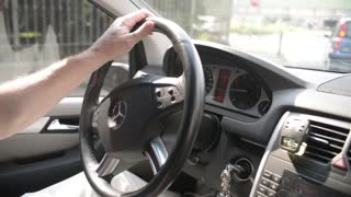 A man drives Mercedes, turn the steering wheel of a vehicle