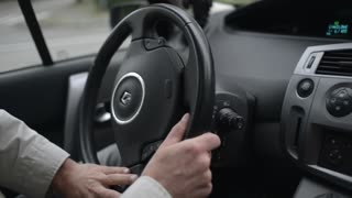 A man drives Renault, turn the steering wheel of a vehicle