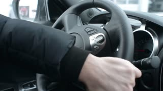 A man extreme drives Nissan, turn the steering wheel and use the Hand brake