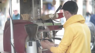A man prepares a coffee outdoors in the coffee machine
