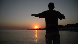 A man winner raises his hands to the sun at sunset