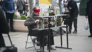 A street musician plays the bottles in the center of Milan, Italy