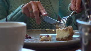 A woman eating cake at the mall cafe - close shot