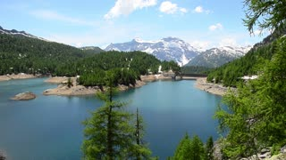 Alpine Lake Reservoir on a background of snow-capped peaks of Alps