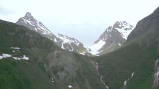 Alps in summer. Snow-covered peaks and green grass