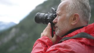 Alps. Male photographer taking pictures against the background of mountains