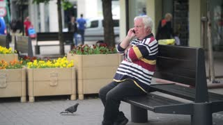 An elderly man with a mobile phone sitting on a bench