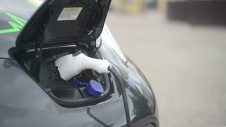 an electric car getting charge from the power outlet, outdoor street car charger