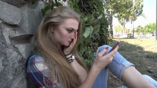 Angry upset Girl chating with Mobile Sell Phone sitting on the Ground
