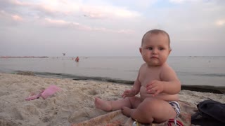 Baby girl playing in the sand on the sea shore beach