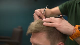 Barber Cuts The Hair Of The Client With Scissors At A Barber Shop