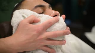 Barber Puts Hot Towel On Customer's Face For Shaving - close up