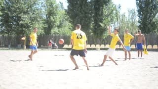 Beach football soccer - players lead the ball, trying to score a goal