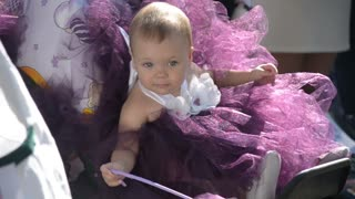 Beautiful baby in a carriage decorated with pink bows