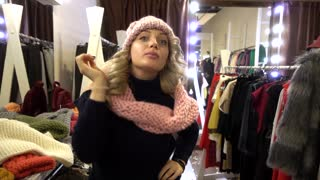 Beautiful Blonde young Woman shopping in a Clothing Store in a Mall looks Mirror