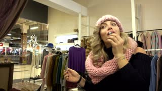 Beautiful Blonde young Woman shopping in a Clothing Store in a Mall paints lips with lipstick