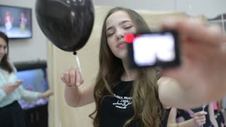 Beautiful Girl brunette make Selfie with GoPro camera  posing with black balloon