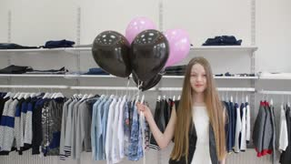 Beautiful Girl brunette posing with black balloons in Clothes Store