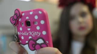 Beautiful Girl Model Brunette makes Selfie with Mobile Hello Kitty Case