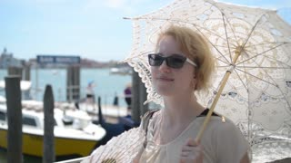 Beautiful sexy blonde woman with an umbrella and a fan near the pier of Venice.