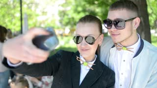 Beautiful young friends boy and girl doing selfie photos on mobile phone in park