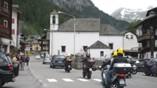 Bikers ride the road through a small alpine town in summer