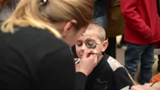 Body art artist draws on the boy's face - happy children