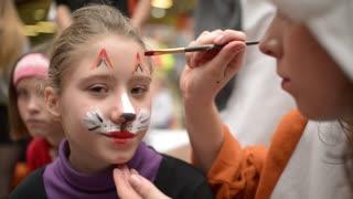 Body art artist draws on the girl's face