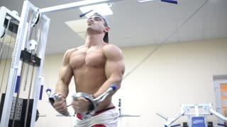 bodybuilder man doing exercise for pectoral muscles in the Gym