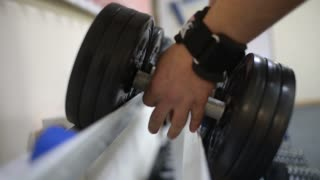 Bodybuilder man doing exercises with dumbbells in the Gym