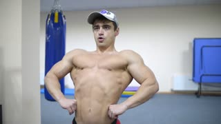 Bodybuilder posing in front of a mirror - straining muscles