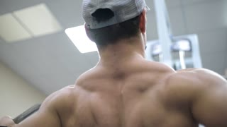 bodybuilder shakes his back muscles in the machine