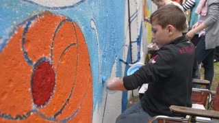 Boy disable on a wheelchair draws paint on the fence wall