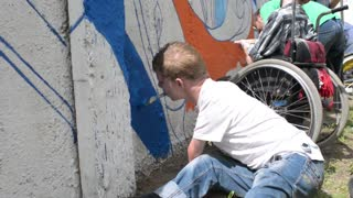 Boy disable on a wheelchair draws paint with brush in mouth