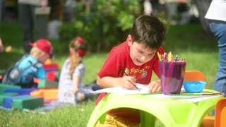 boy draws pencils on a paper in the summer park