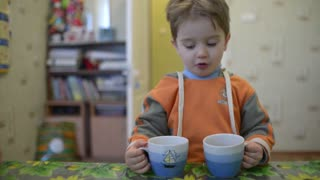 Boy drinks tea from a big cup in the kitchen at home